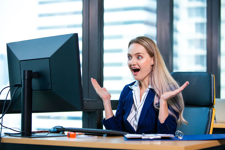Surprised young woman looking at computer in office