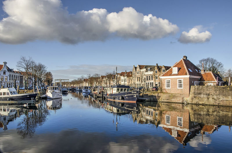 Sailboats moored on canal by houses against sky