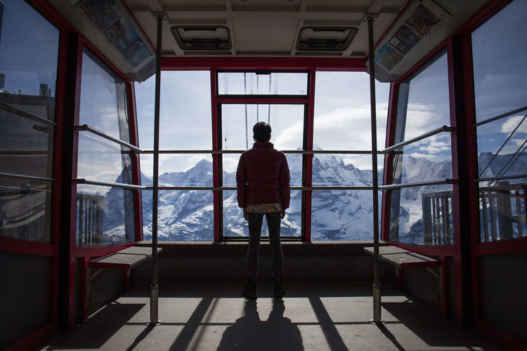 Rear View Of Person Looking Towards Snowcapped Mountains Through Ski Lift Windows