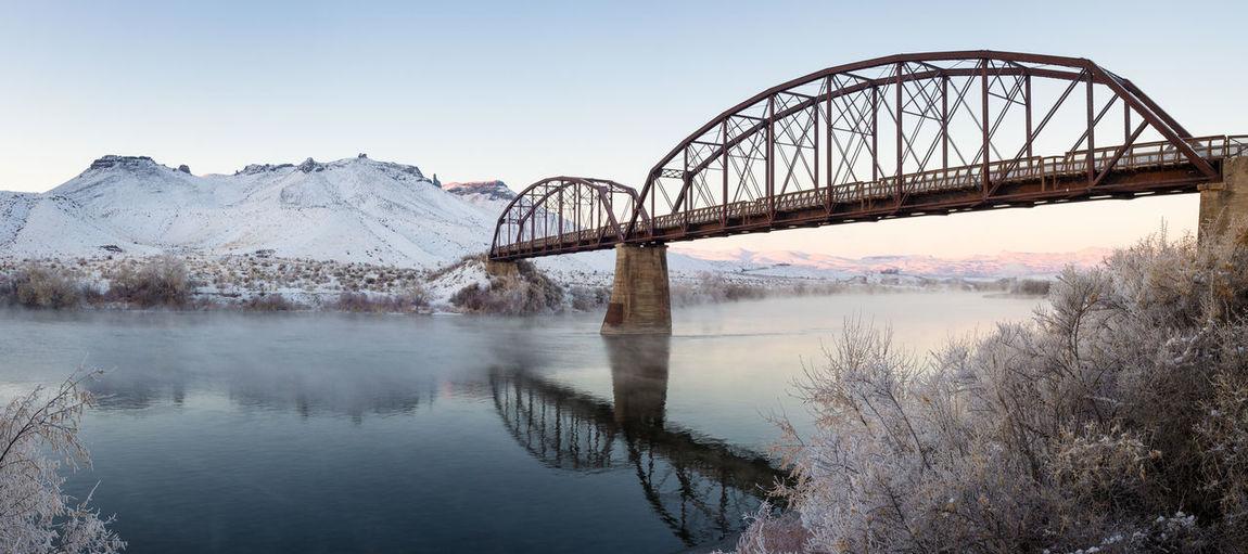 Bridge over lake against clear sky