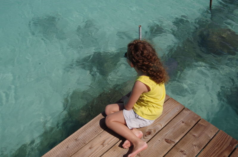 High angle view of girl sitting on pier over sea