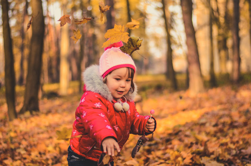 Pretty girl playing with yellow leaves in the autumn forest
