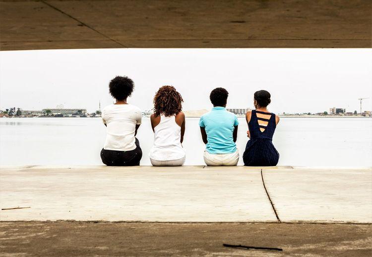 Rear view of friends sitting on promenade