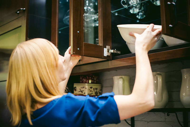 Woman taking bowl from kitchen cabinet