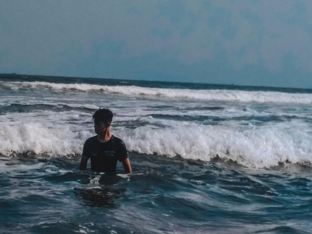 FULL LENGTH OF MAN AT SEA SHORE AGAINST SKY