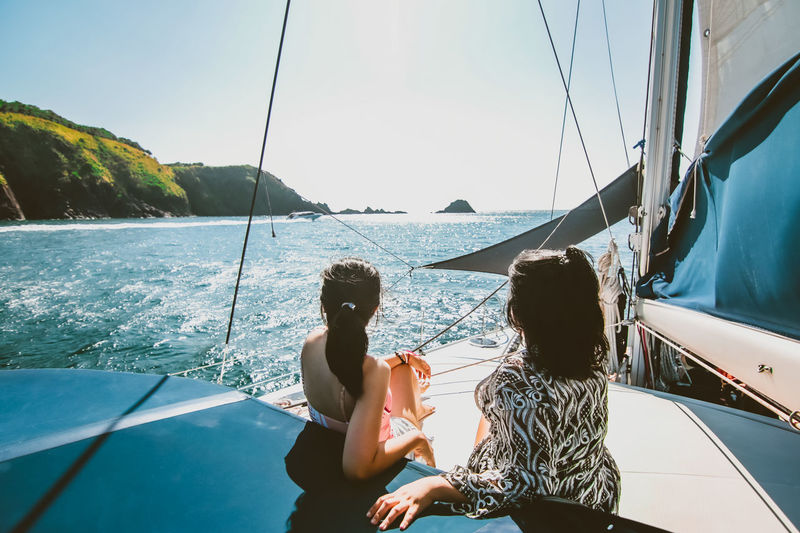 Female friends relaxing on yacht during sunny day