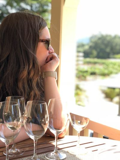 Thoughtful woman sitting with empty wineglasses at table