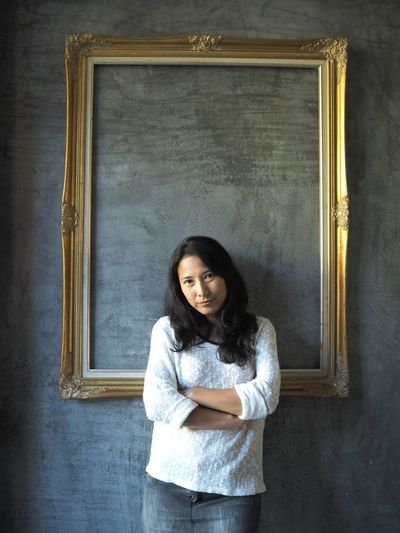 Portrait of woman with arms crossed standing against wall
