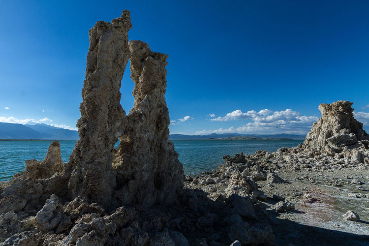 Scenic view of rock and sea against blue sky