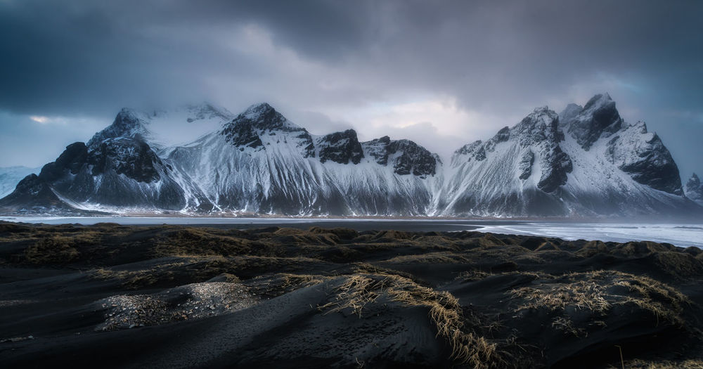 Panoramic view of snowcapped mountains by sea against cloudy sky