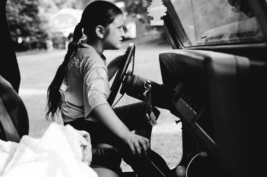 Sitting Driving Child Pretending Play Steering Wheel Car Automobile Day Real People Playing Outdoors Fun One Person Girl