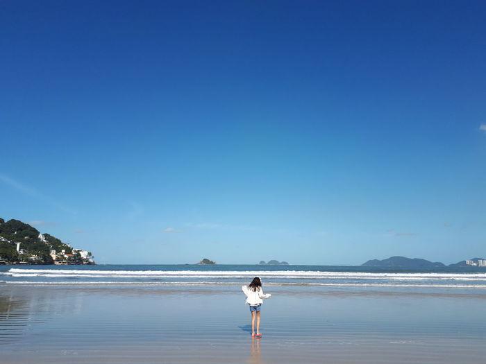Girl standing at beach against blue sky