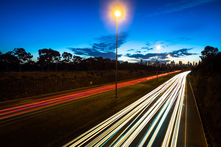 Light trails on road against blue sky at night