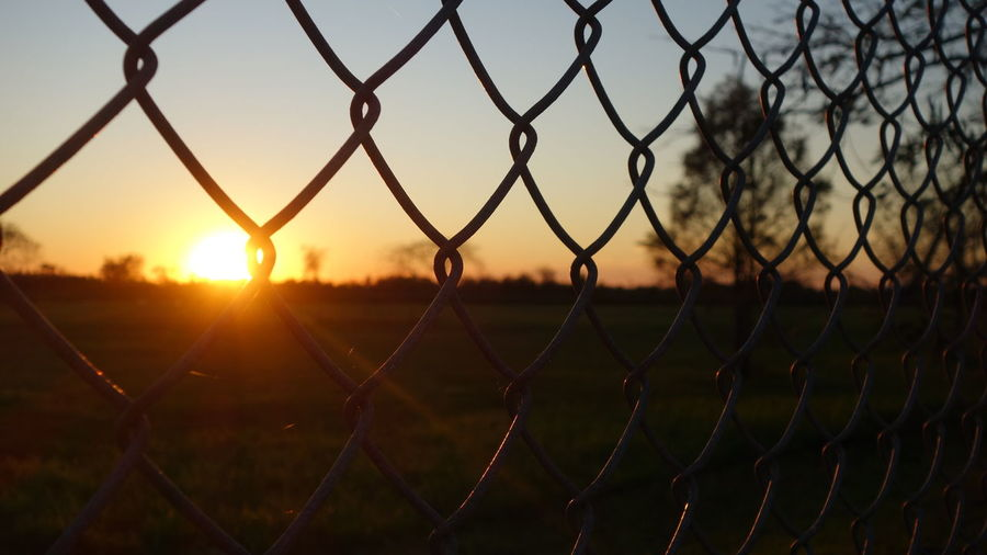 Close-up of chainlink fence during sunset