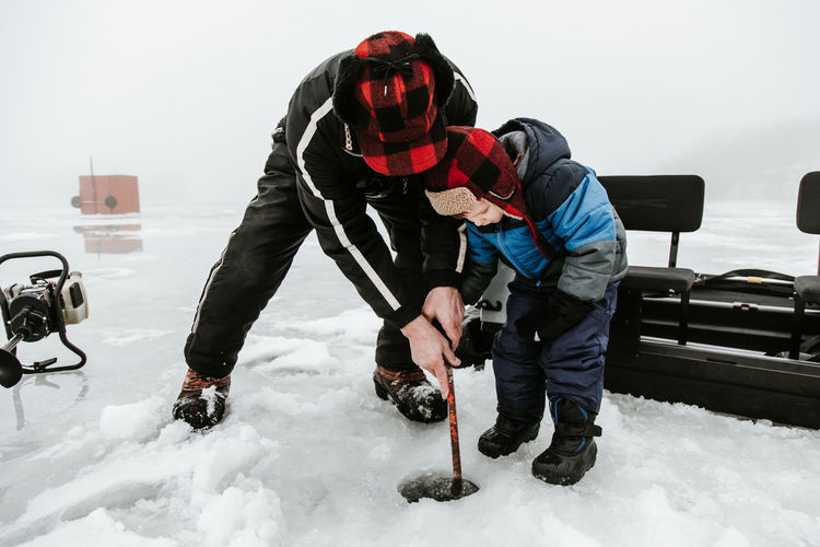Senior Man With Grandson Holding Metal Rod On Frozen Lake