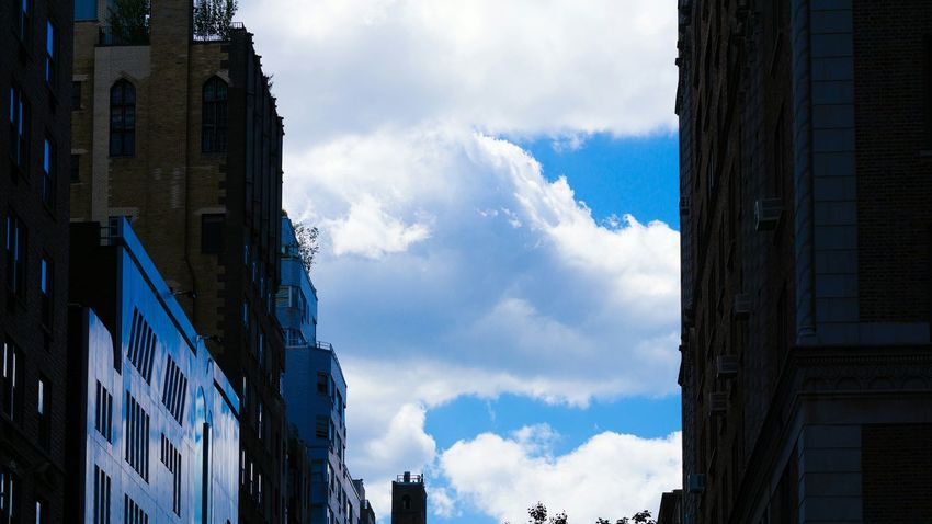 Mostly cloudy. NYC Street Photography Buildings Reflections Clouds And Sky Looking Up Vibrant Colors 16:9 Sony A6000 Project365
