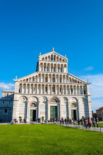 The Cathedral dedicated to Santa Maria Assunta, in Piazza dei Miracoli in Pisa. UNESCO World famous site, located in beautiful Tuscany Architecture Built Structure Building Exterior Sky Grass Blue Nature Travel Travel Destinations Tourism Day Building History The Past Lawn Plant People Incidental People Outdoors Group Of People Pistil Piazza Dei Miracoli Tower Learning Pisa Pisa Tower Pisa Cathedral