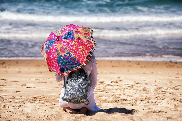 Rear view of woman with umbrella kneeling at beach during sunny day