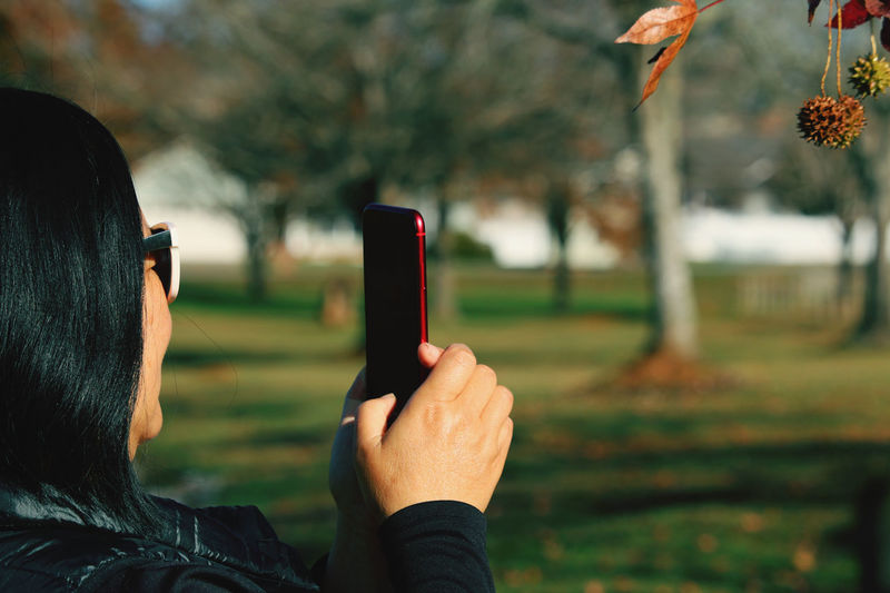 Close-up of woman photographing with smart phone in park