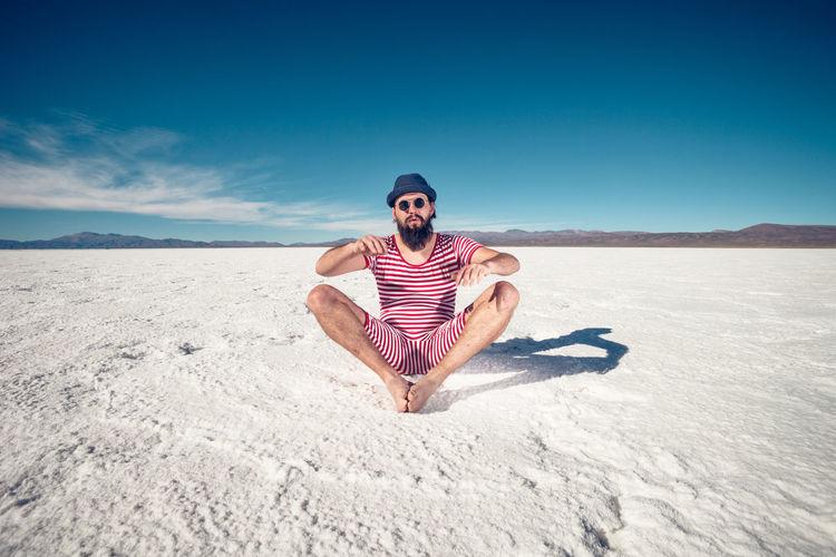 Full length of young man on sand in desert against sky
