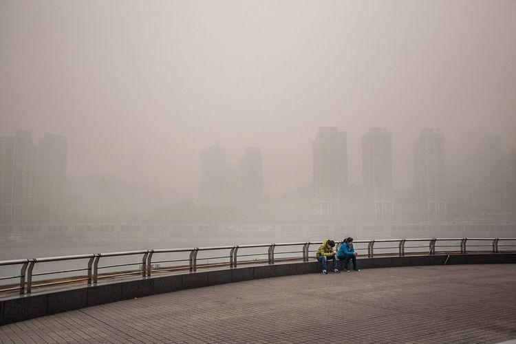 People on bridge in city against sky during rainy season