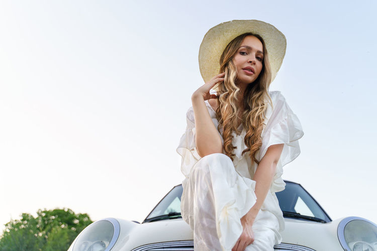 Young woman in hat standing against sky