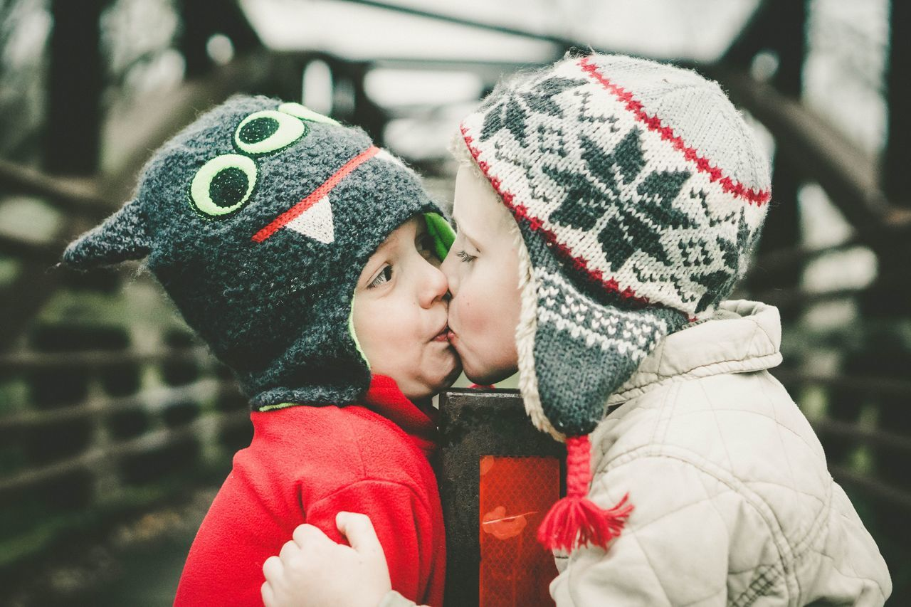 Close-up of brothers kissing while standing at bridge