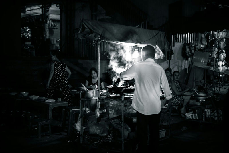 Cooking on the street. Hoi An, Vietnam. Real People Rear View Street Cooking Hoi An Hoi An, Vietnam Street Stall Night Market Market Stall Cooking Travel Destinations WeekOnEyeEm EyeEm Gallery Check This Out EyeEm Best Shots Exceptional Photographs Bestoftheday Malephotographerofthemonth Travel Photography Black And White Photography Blackandwhite Central Vietnam Snap A Stranger