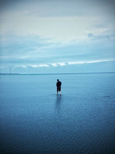 Full Length Rear View Of Man Walking On Shore