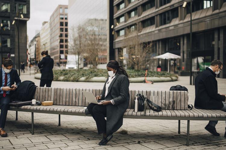Men sitting on bench in city