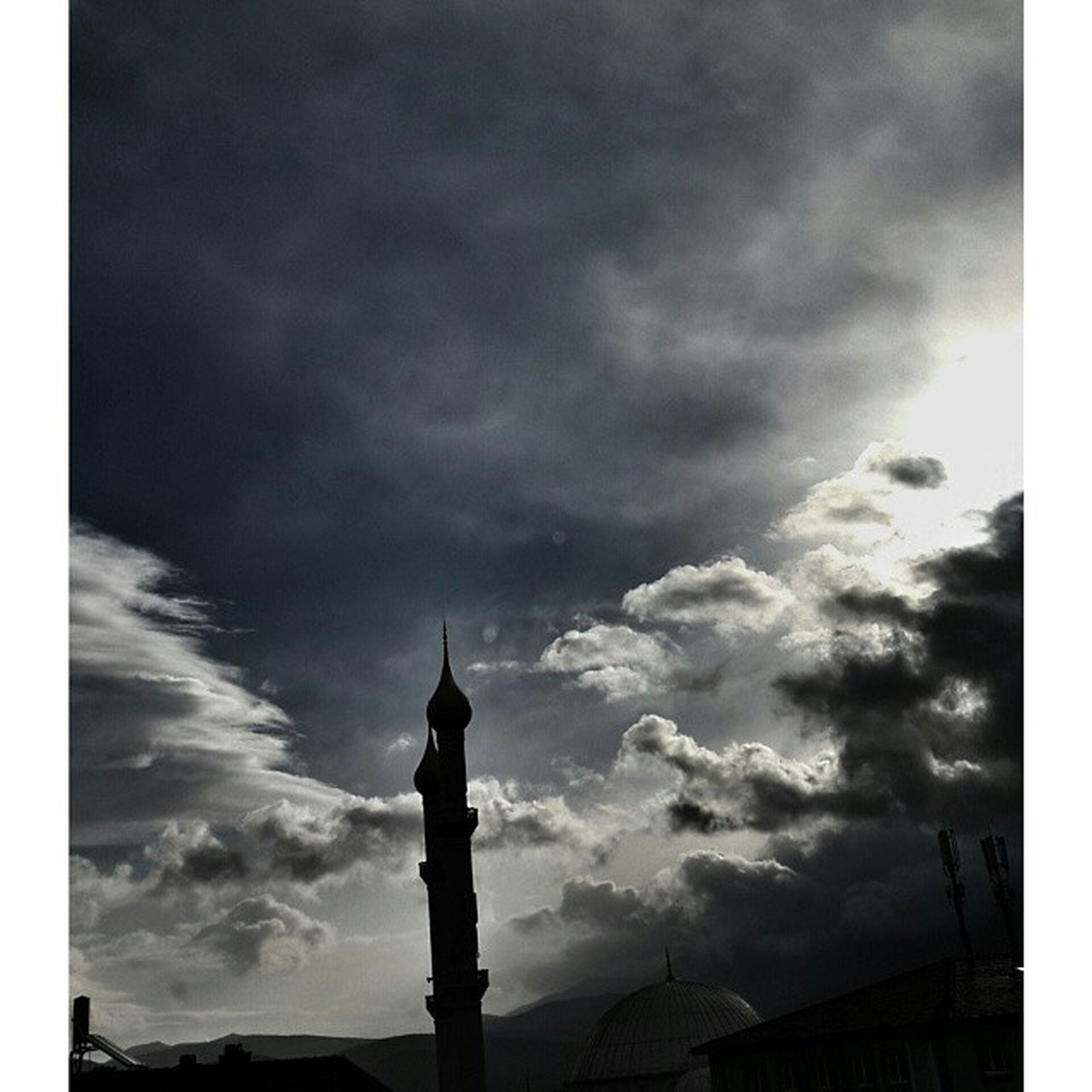 low angle view, sky, cloud - sky, architecture, cloudy, built structure, building exterior, cloud, silhouette, weather, high section, overcast, transfer print, auto post production filter, street light, outdoors, building, dusk, no people, nature