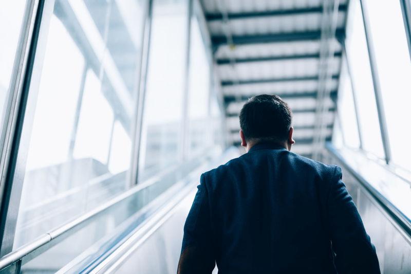 Rear view of businessman on escalator