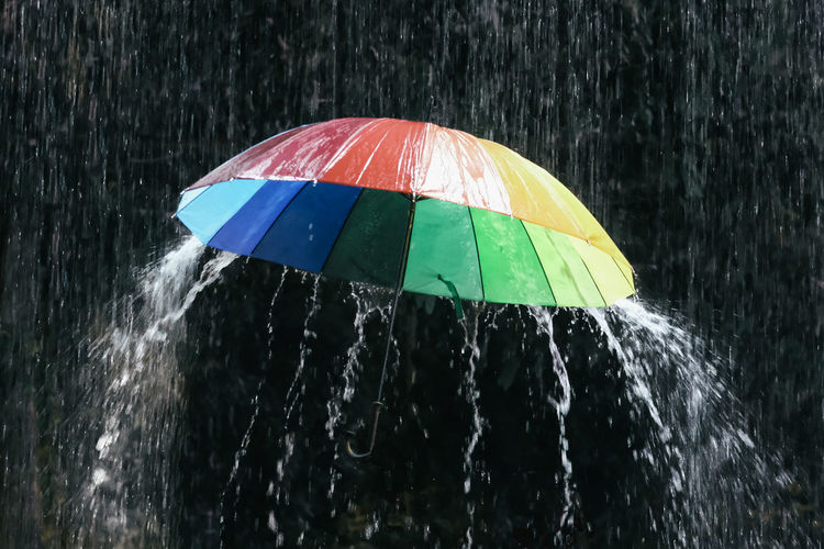 Water drops on multi colored umbrella during monsoon