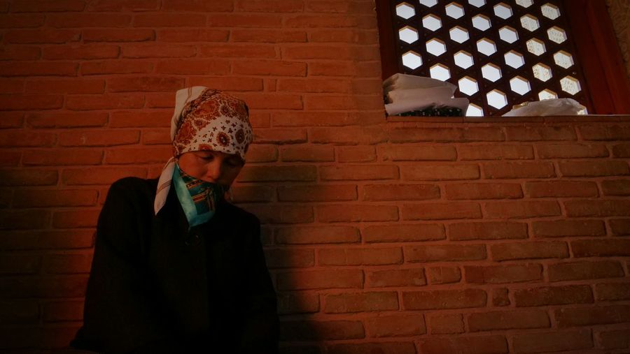 Man with headscarf standing against brick wall