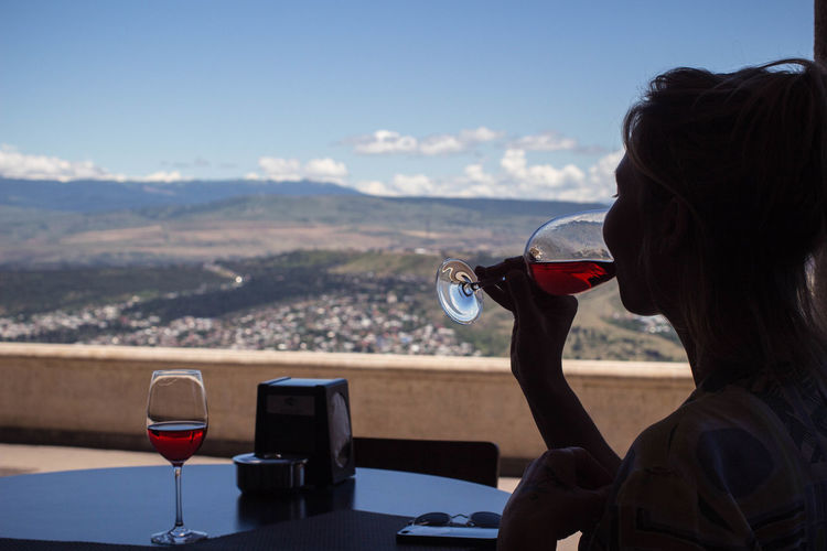 Woman drinking wine at table against landscape