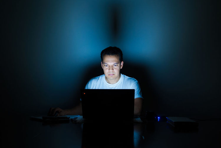 Man using a laptop at night. Internet Addiction Screen Light Screenlight Laptop Work Alone Alone In The Dark Lonelyness Laptop Laptop User The Color Of Technology