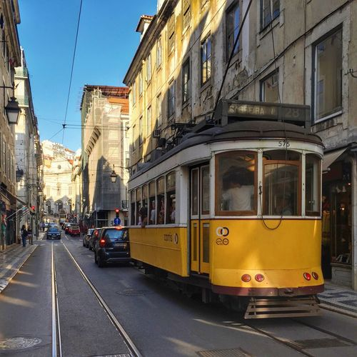 Tramway On City Street Amidst Buildings Against Clear Blue Sky