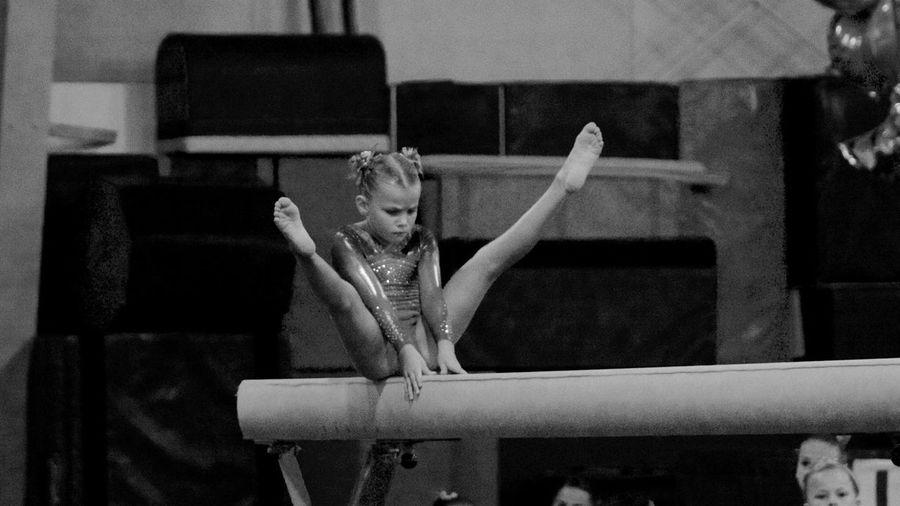 Girl performing gymnastics on pole