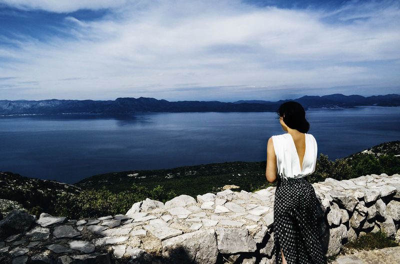 Beauty In Nature Cloud - Sky Day Distant Idyllic In Front Of Loneliness Mountain Nature Non-urban Scene Outdoors Person Rear View Relaxation Remote Scenics Sitting Sky Solitude Standing Tourism Tranquil Scene Tranquility Water Woman