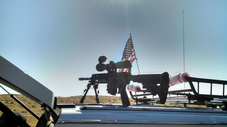 Machine Guns On Vehicle By American Flag Against Sky