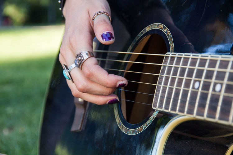 Close-Up Of Woman Playing Guitar At Public Park
