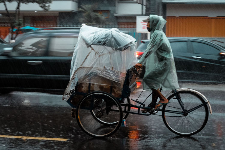 Raining session in Indonesia, Rain Raining Transportation Mode Of Transportation Car Motor Vehicle Land Vehicle City One Person Wet Street Full Length Real People Day Rainy Season Architecture Motion Monsoon Bicycle Outdoors