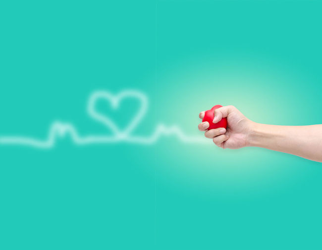 Cropped hand holding red heart shape against turquoise background