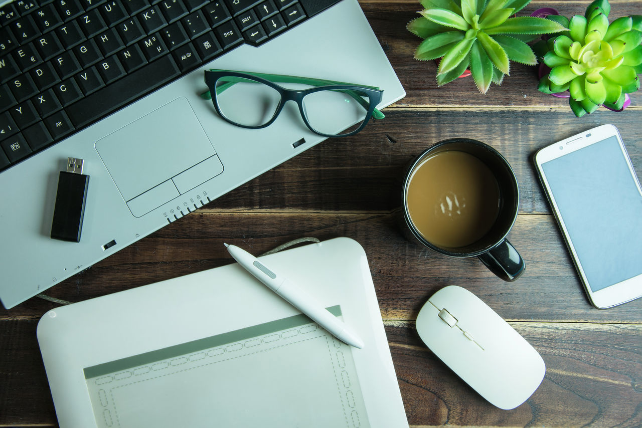 technology, computer keyboard, table, wireless technology, laptop, indoors, computer, desk, communication, connection, pen, keyboard, high angle view, no people, paper, book, internet, drink, eyeglasses, diary, stapler, day, freshness, close-up