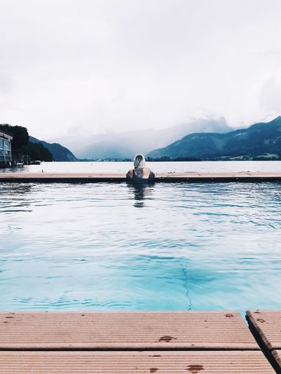 Rear view of woman swimming in infinity pool by lake against sky