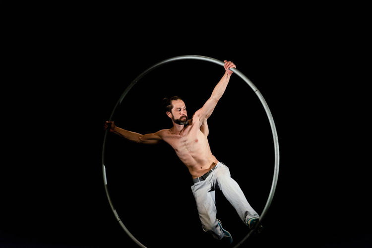 Circus Acrobat Adult Agility Arms Raised Arts Culture And Entertainment Balance Black Background Circle Circus Expertise Flexibility Geometric Shape Holding Human Arm Indoors  Motion One Person Performance Plastic Hoop Shape Skill  Standing Strength Studio Shot