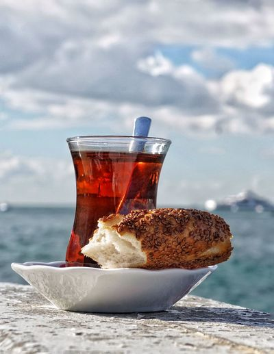 Close-Up Of Turkish Tea And Bagel Against Cloudy Sky On Sunny Day