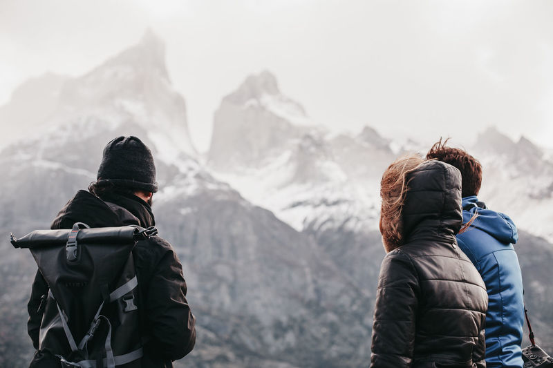 Friends Standing Against Snowcapped Mountains