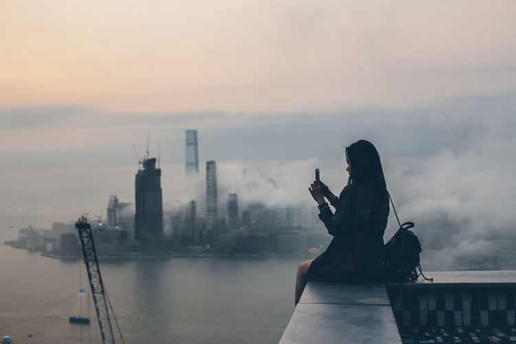 Woman sitting on retaining wall against sky in city