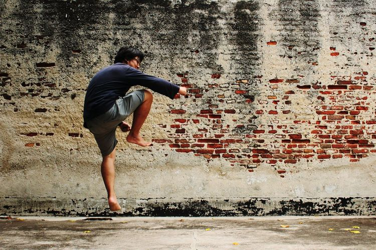 Man jumping against old brick wall
